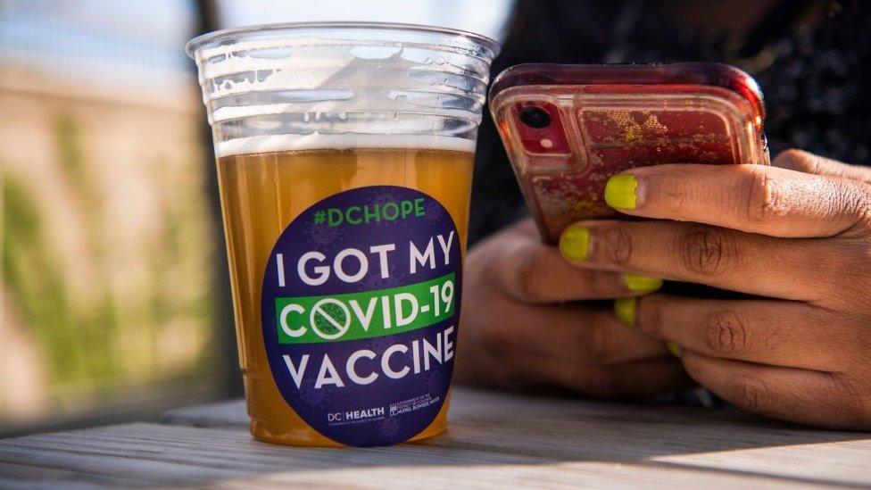 美國華盛頓某疫苗接種中心外一位接種完畢的女士在享用免費派發的啤酒(6/5/2021)