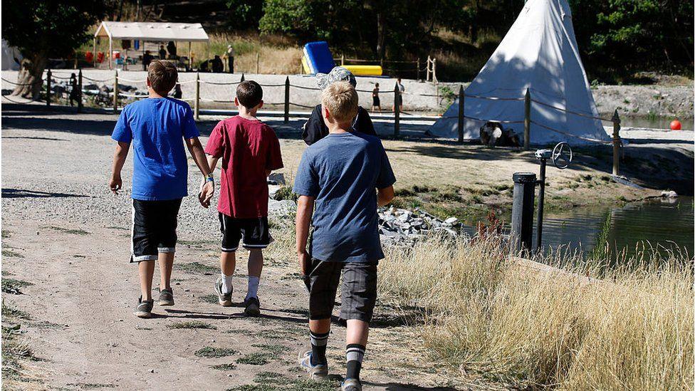 فتية من الكشافة الأمريكيين يتجولون في أحد أماكن التخييم.