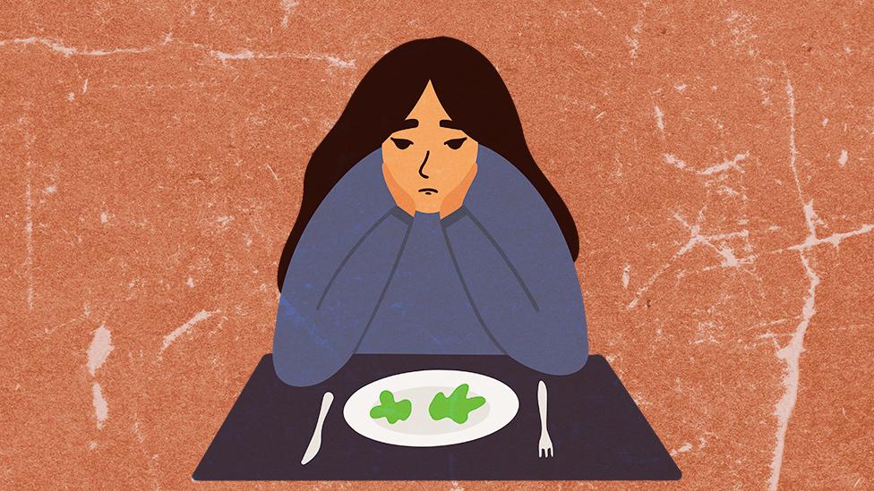 Devojka sedi za stolom sa skoro praznim tanjirom