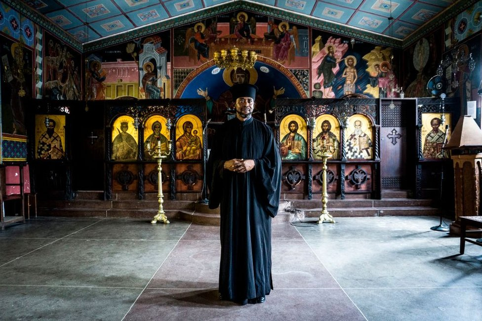 A priest stands in front of an ornate altar
