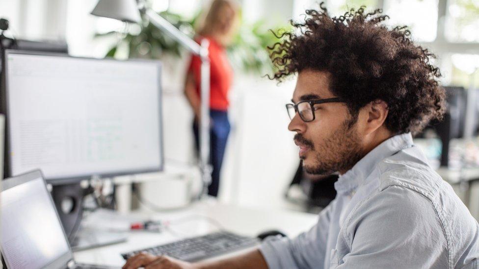 Hombre frente a computador