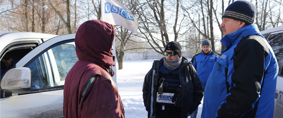 OSCE observers talk with a local resident woman (L) in Ukraine-controlled town of Avdiivka on 30 January