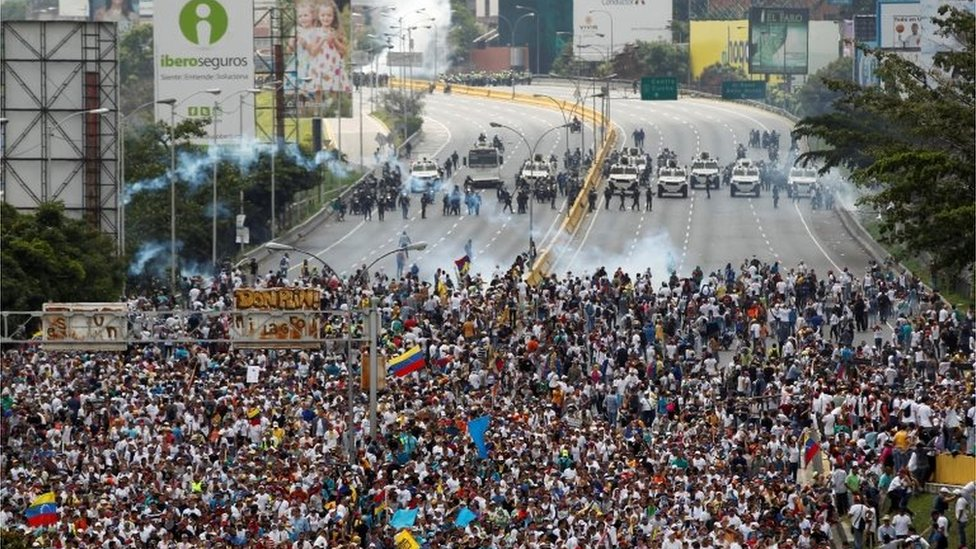 """Demonstrators clash with riot police during the so-called """"mother of all marches"""" against Venezuela's President Nicolas Maduro in Caracas, Venezuela April 19, 2017."""