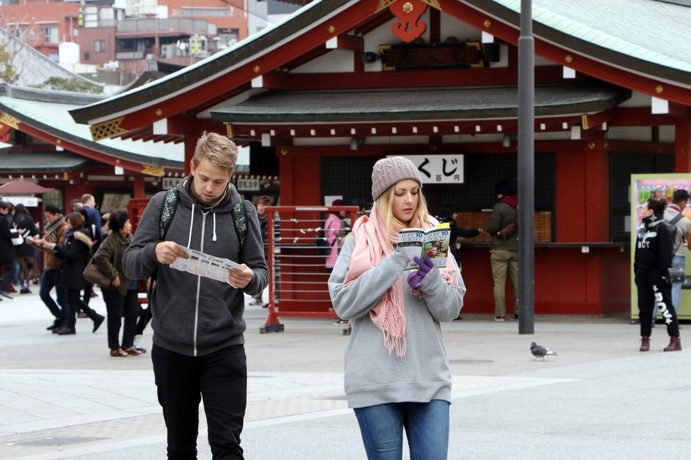 This picture taken on 3 March 2015 shows foreign tourists looking at a guide book and a map at Sensoji temple at Tokyo's Asakusa district