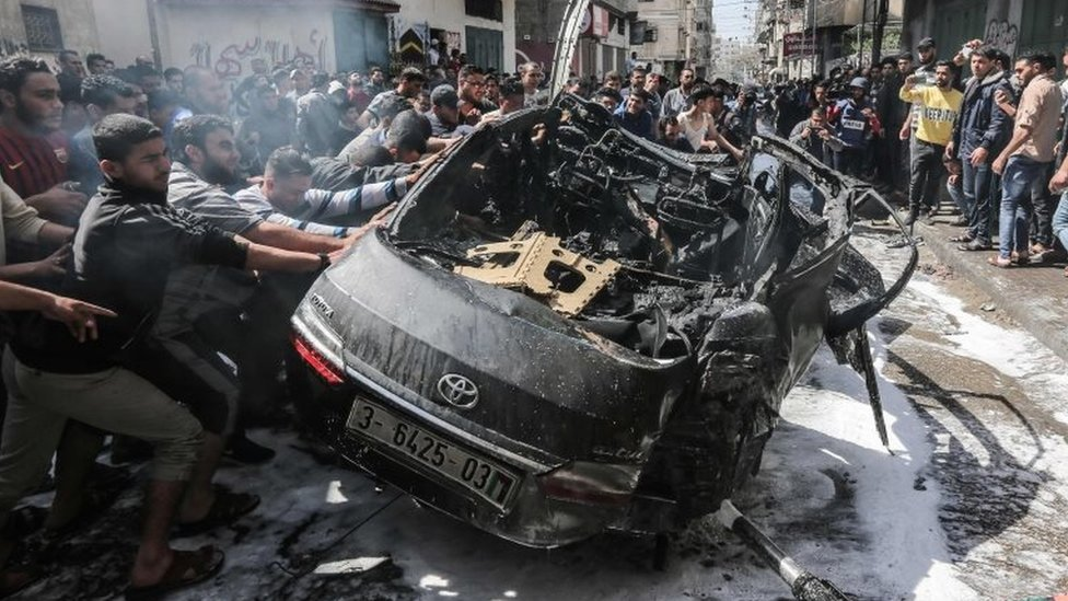 Palestinian emergency personnel try to put out the fire on a car