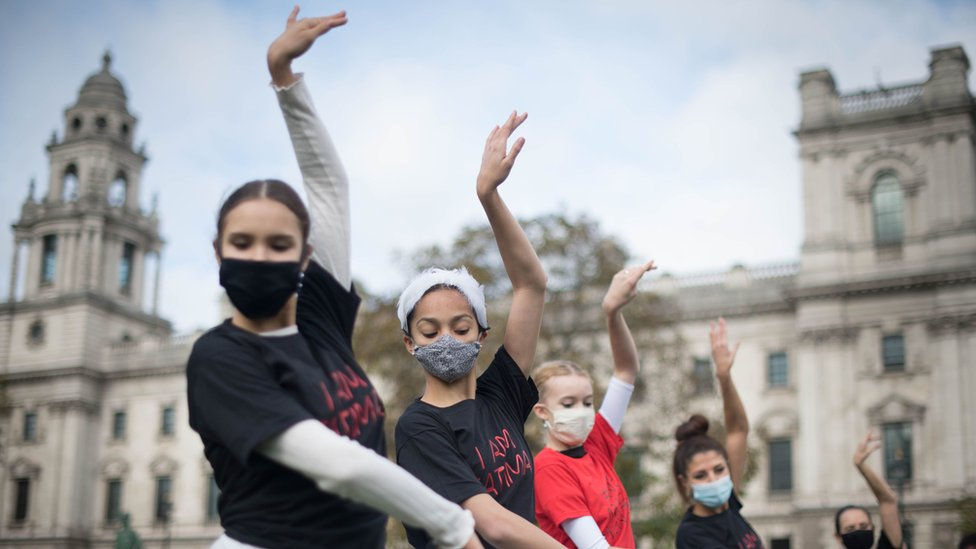 Young ballet dancers wearing masks perform in Parliament Square, London, as part of protest for more funding for the arts