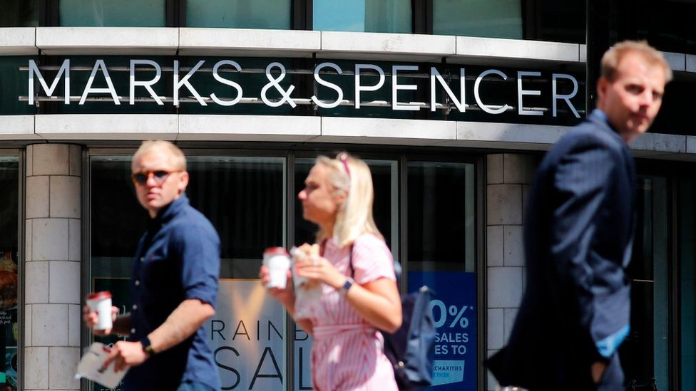 Shoppers walk past M&S in central London