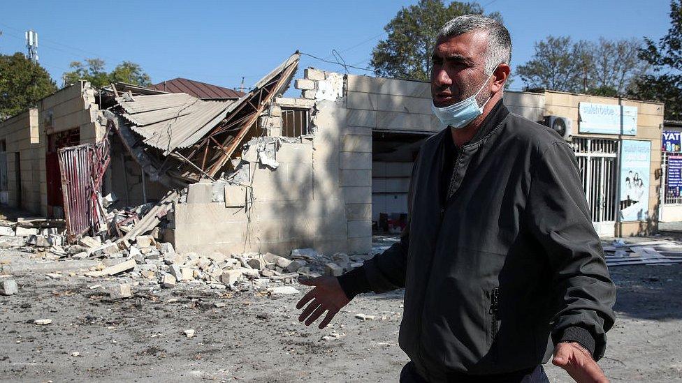 A man walks by a market in Tartar, Azerbaijan, damaged in a shelling attack