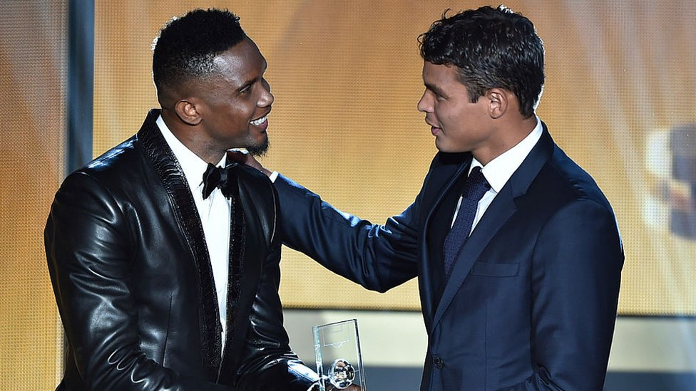 Brazil defender Thiago Silva (R) receives an award from Cameroon Samuel Eto'o