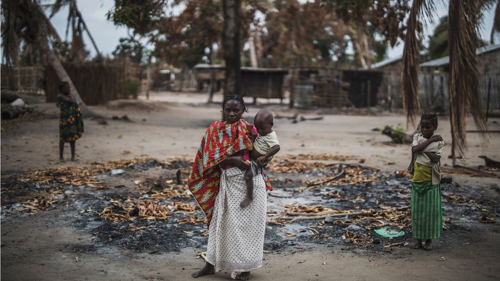 A woman holds her younger child while standing in a burned out area after an on the village of Aldeia da Paz outside Macomia, Mozambique - 24 August 2019