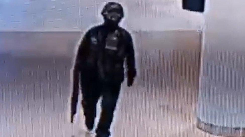 Imagen del sospechoso en el centro comercial con un rifle.