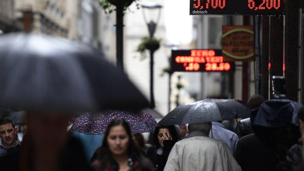 Personas se cubren de la lluvia en Buenos Aires