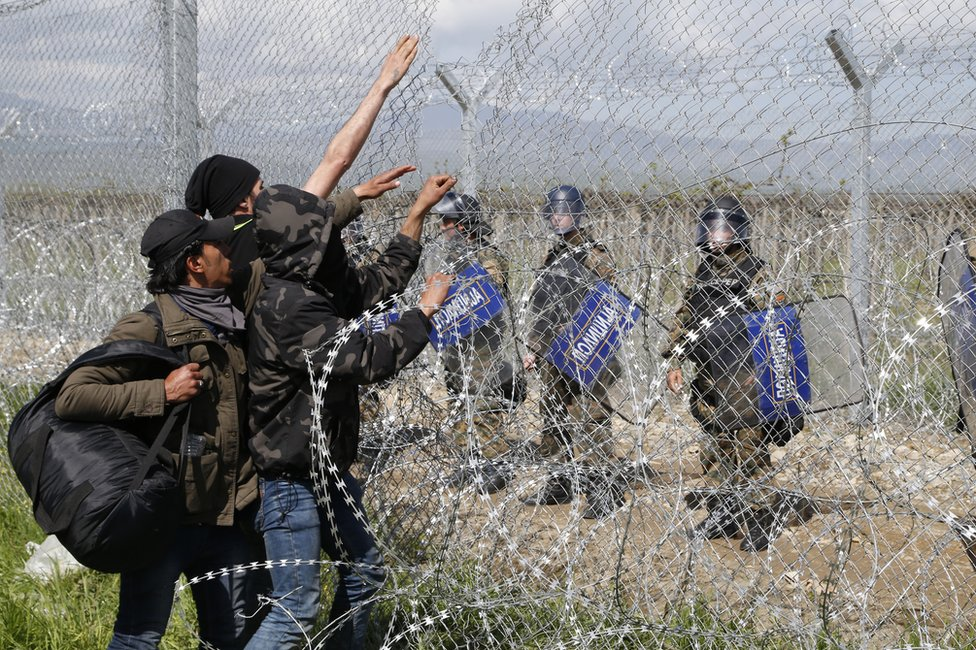 Migrants face Macedonian police on the Greek border at Idomeni, 10 April