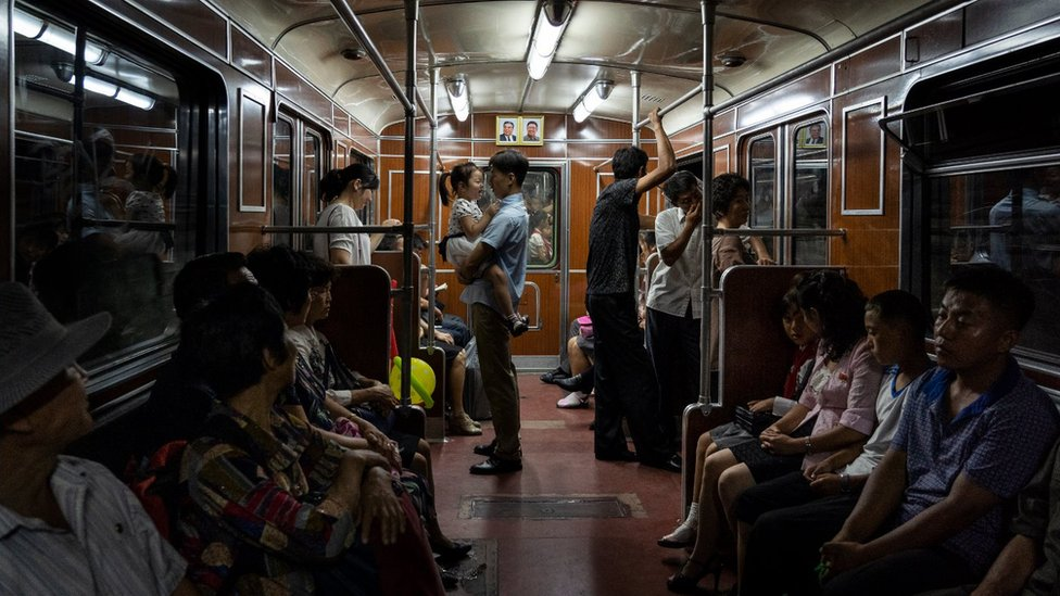 A family rides the metro in Pyongyang