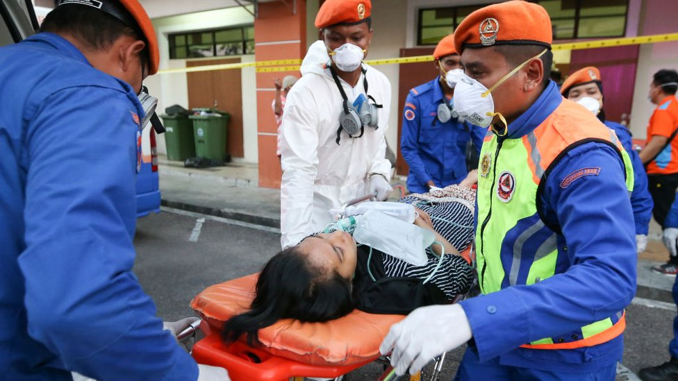 Emergency personnel evacuate a victim to a hospital after a toxic chemical spill in Pasir Gudang