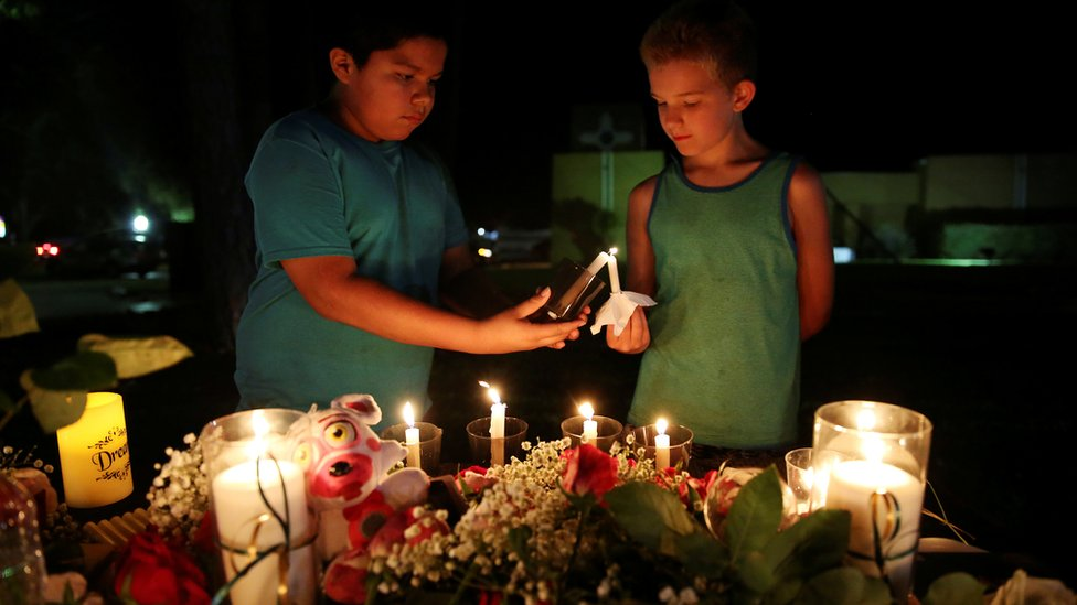Christian Cardenas 10, helps Jaydon Johnson 8, light a candle during a vigil for the victims of a shooting at Santa Fe High School
