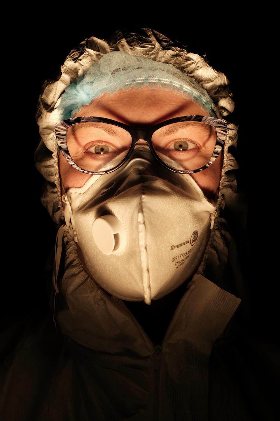 Seorang perawat mengenakan masker dengan latar belakang ruangan yang gelap
