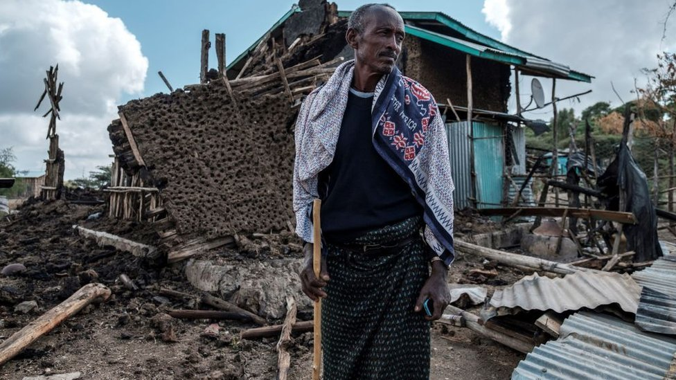 رجل يقف وسط دمار قريته في تيغراي