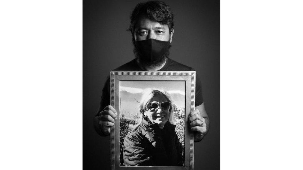 Mário posa com máscara segurando um retrato da mãe