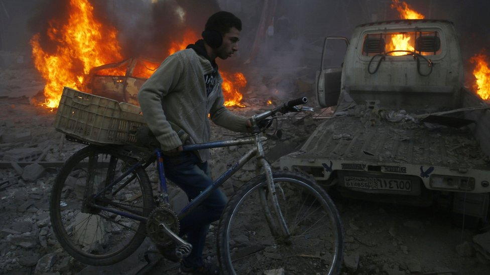 A man carries his bicycle past debris and burning cars following air strikes in the Damascus suburb of Hamouria (9 December 2015)