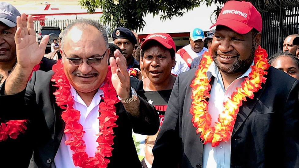 """In this handout photo taken on July 16, 2017 shows then Papua New Guinea prime minister Peter O""""Neill (L) and then finance minister James Marape (R)"""