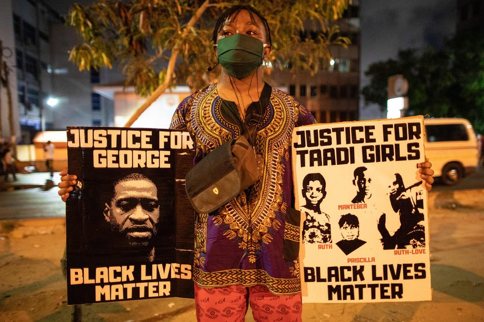 An activist holds placards in Accra, Ghana, during the protest.