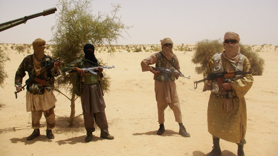 In this file photo from 24 April 2012, fighters from Islamist group Ansar Dine stand guard during a hostage handover in the desert outside Timbuktu, Mali.