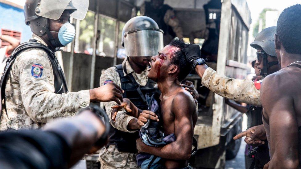 Hombre herido y militares en Haití