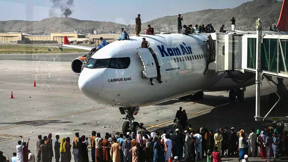 People clamber on top of planes as smoke rises in the distance