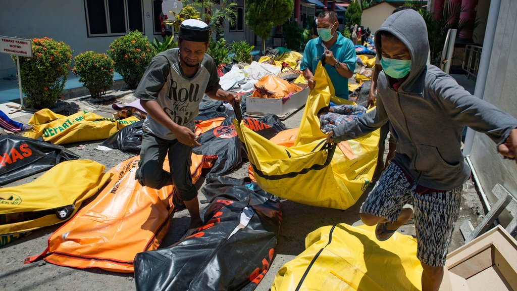 Ljudi nose tela žrtava u bolnicu u Paluu. Septembar 2018