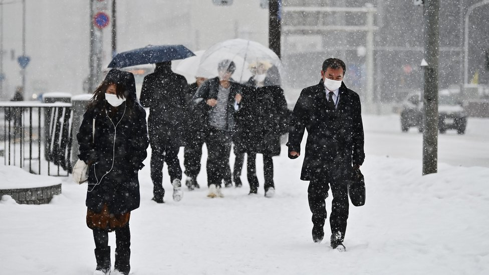 People in Hokkaido wear masks and walk through snowfall (Feb 2020)