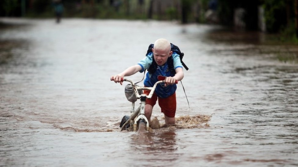A child pushes his bicycle through a flooded road in Honduras