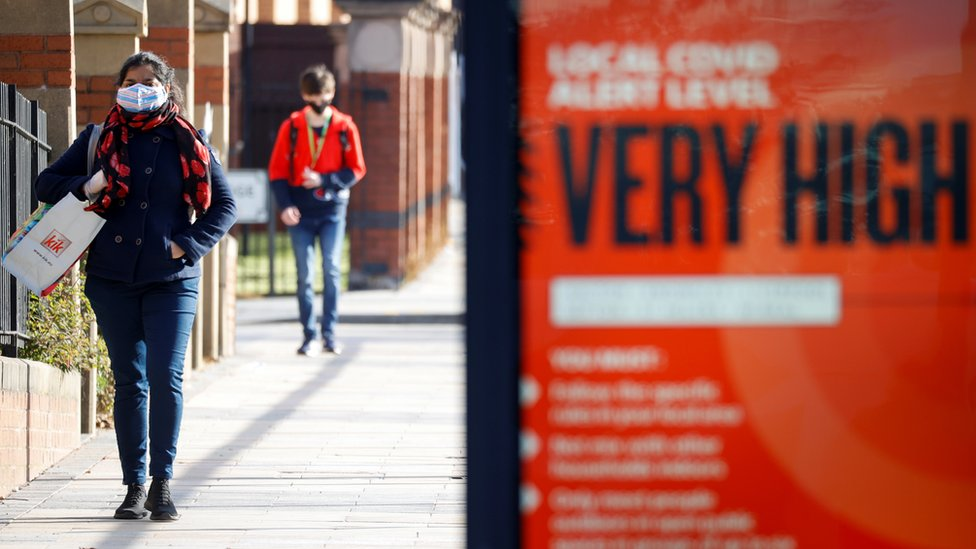 """Person in Liverpool walking past a poster saying Covid levels are """"very high"""""""
