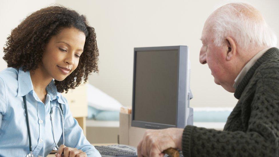 Médico hablando con un paciente mayor.