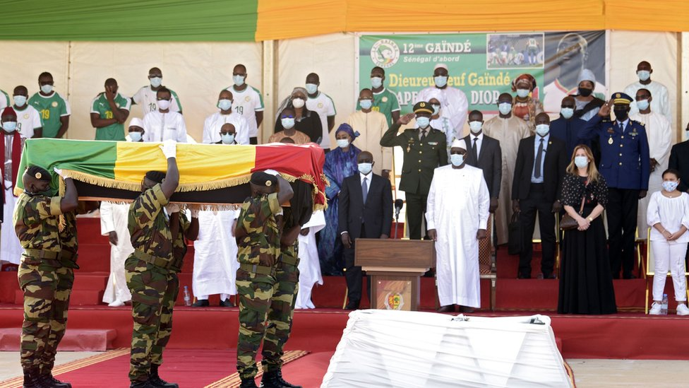 Senegal's president Macky Sall (C) and the widow of Papa Bouba Diop, Marion Diop attend a ceremony marking the reception of the coffin of former international Papa Bouba Diop