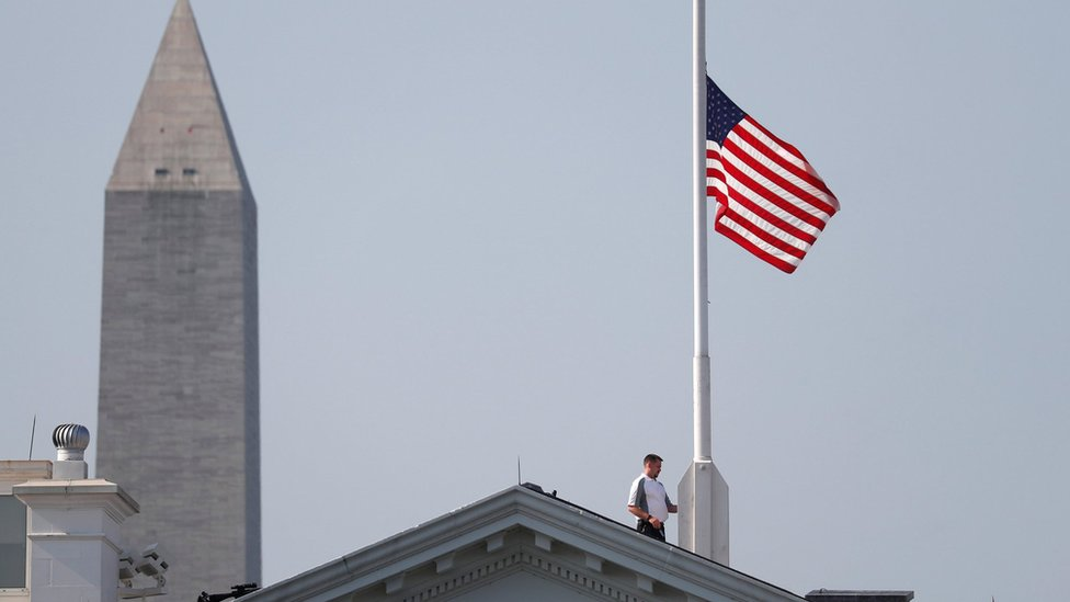 A worker lowers the flag over the White House in Washington to half-staff