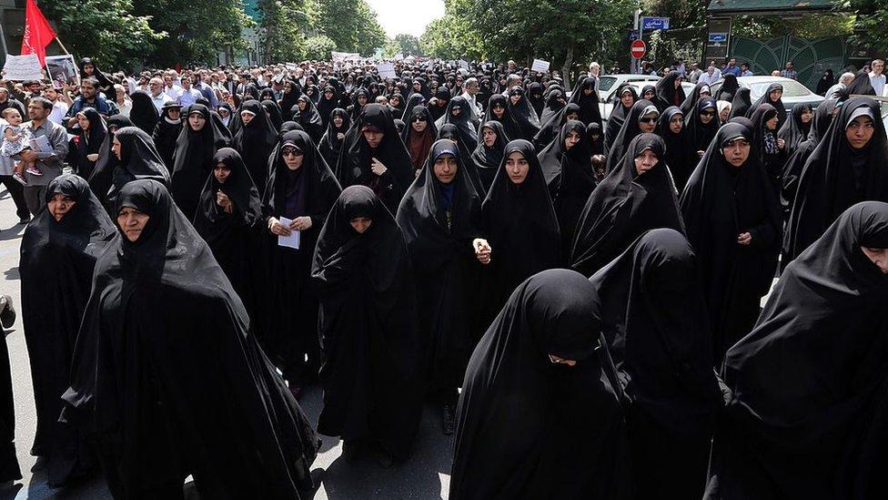 Mujeres vestidas de negro protestan en 2014 para que se mantenga el código de vestimenta.