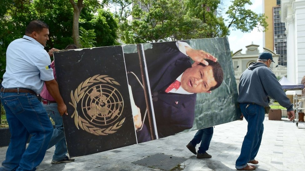 National Assembly employees remove from the building pictures of late President Hugo Chavez, in Caracas on January 6, 2016.