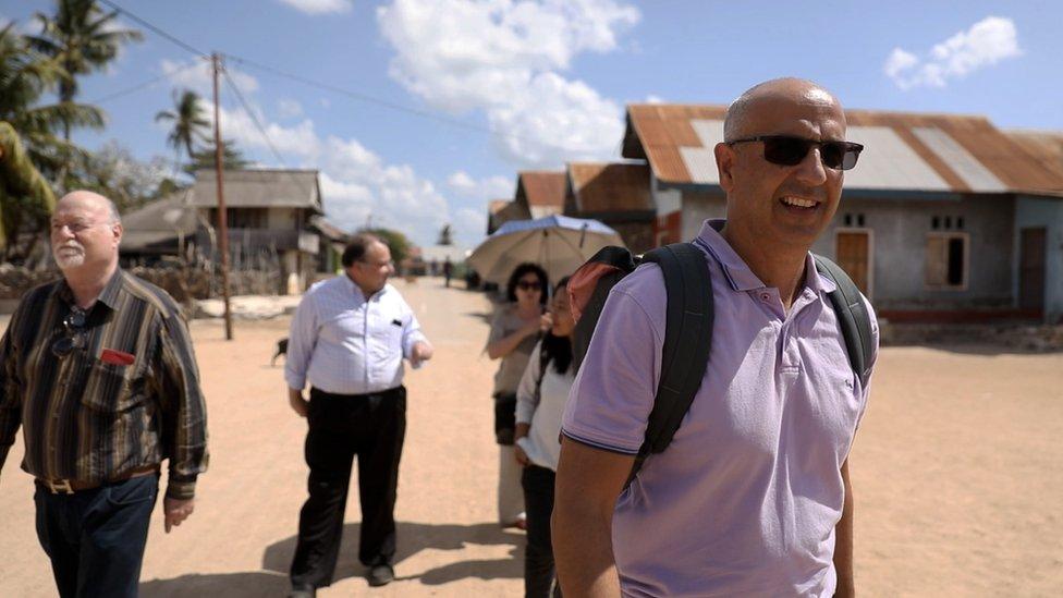 Mark Barrow and others walk in a street in Oelaba village