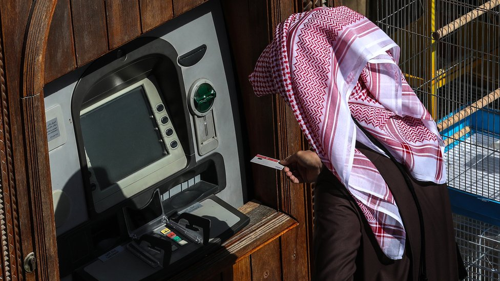 شخص يستعمل ماكينة نقود