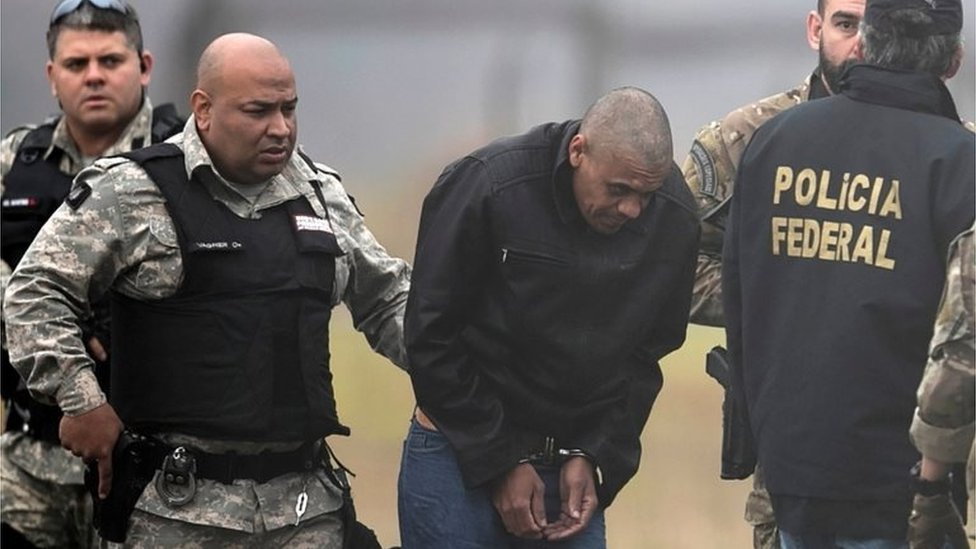Federal Police agents escort Adelio Bispo de Oliveira, suspected of stabbing Brazilian presidential candidate Jair Bolsonaro, to transfer him to a federal prison in Campo Grande, Mato Grosso state, at Francisco Alvares de Assis airport in Juiz de Fora, Brazil, September 8, 2018.