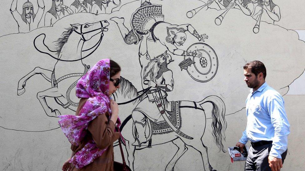 People walk past a mural in Tehran, Iran (25 June 2019)