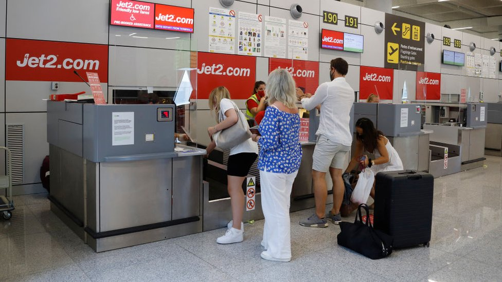 Passengers queue up at the Jet2 check-in desk at Palma de Mallorca airport in Mallorca