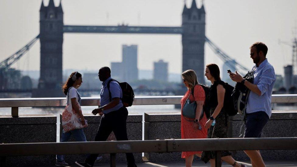 Personas caminando con el Puente de la Torre de Londres al fondo.