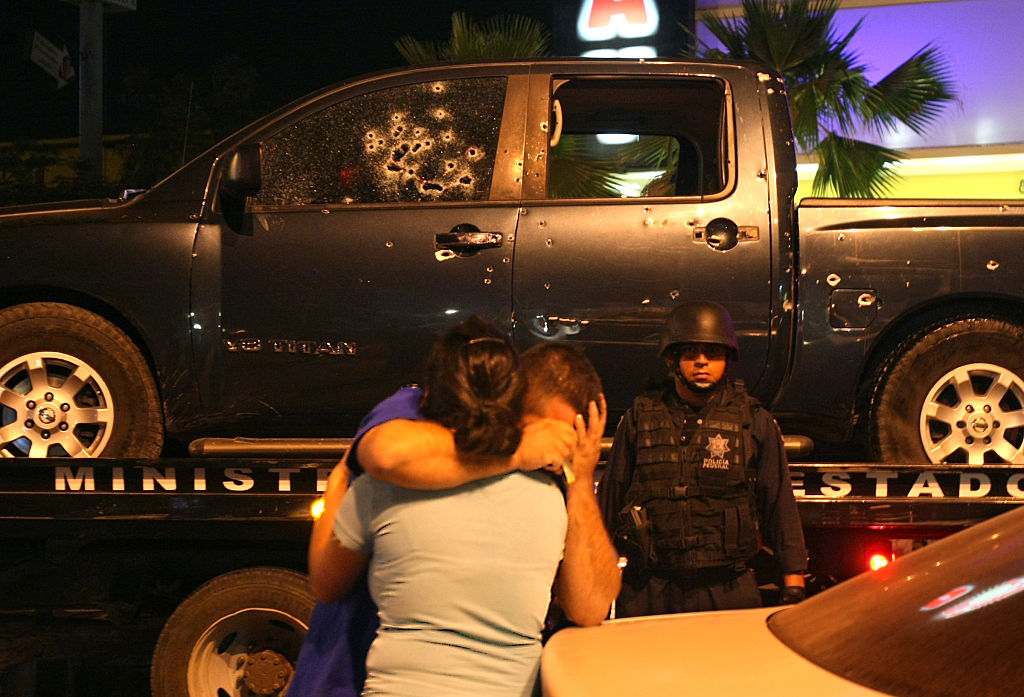 A policeman is consoled by his wife after a fatal shootout between narcos and police in Culiacan