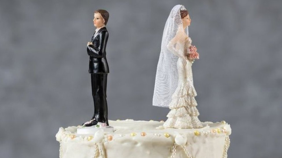 Cake toppers facing away from each other on a wedding cake