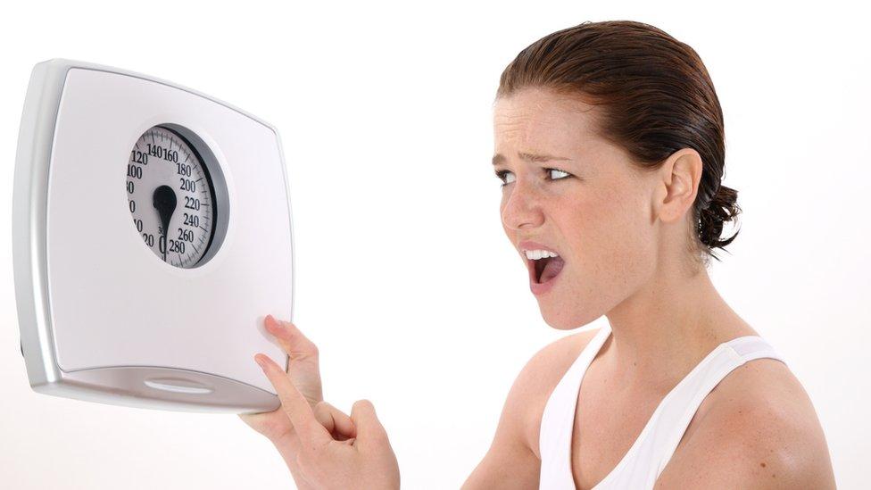 Mujer enfadada mirando a una báscula.