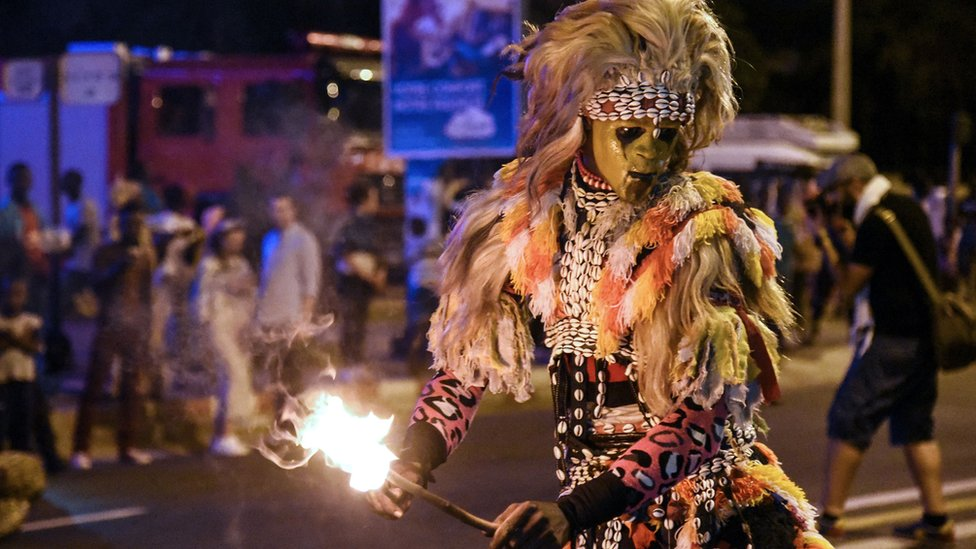 Someone in traditional dress looking like a lion during a carnival in Dakar, Senegal - Saturday 23 November 2019