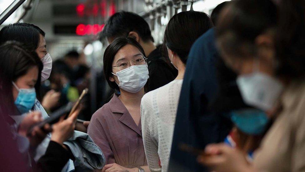 Personas con máscaras en el metro de Pekín.