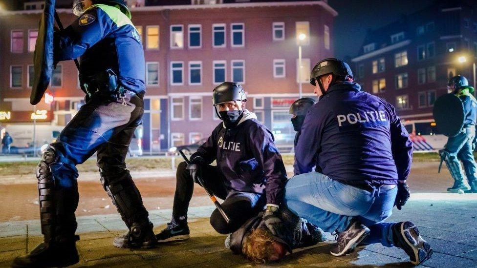 Policías arrestan en Rotterdam a un hombre que participaba en las protestas.